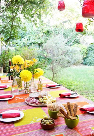 Table set for an outdoor meal in garden and decorated with flowers