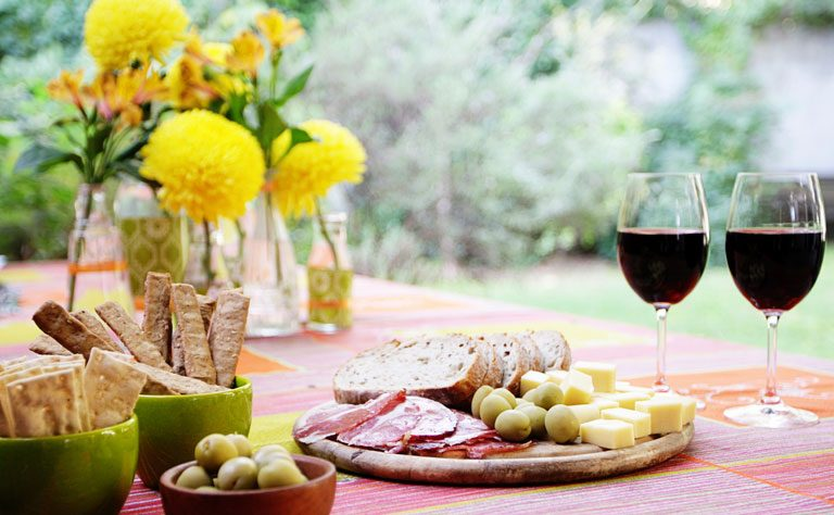 Garden party table with tapas, breadsticks, red wine and yellow flowers