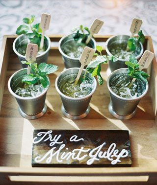Summer cocktails with herb garnish on a rustic wooden tray
