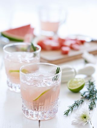 Pink gin with lime and rosemary garnish