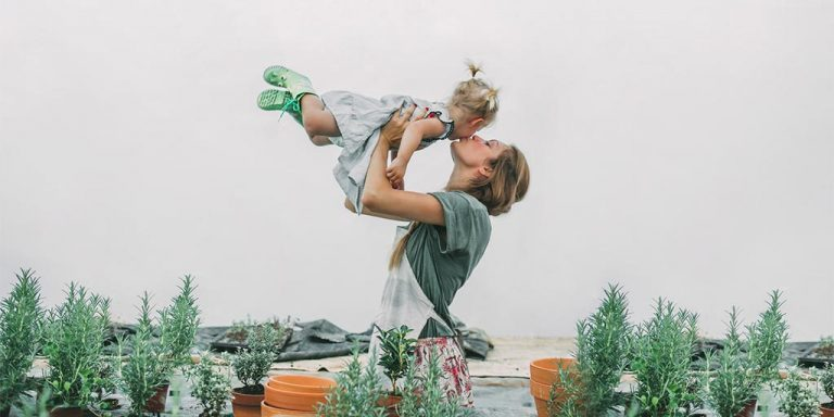 Mother holding and kissing her girl in a garden surrounding.