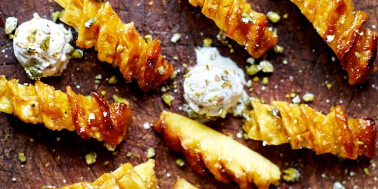 Pineapple coated with crystallised nuts and served with ice cream.