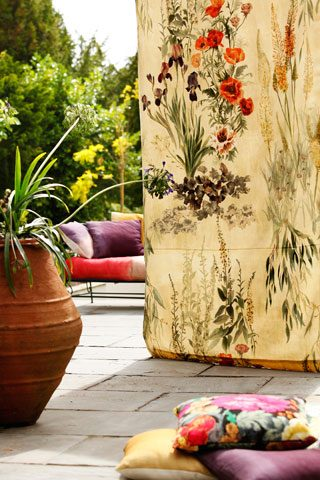 Garden patio decked out with sofa, colourful cushions and floral materials
