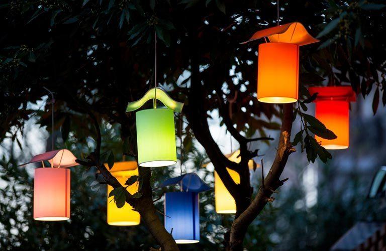Seven colourful, lit lanterns hanging in garden tree
