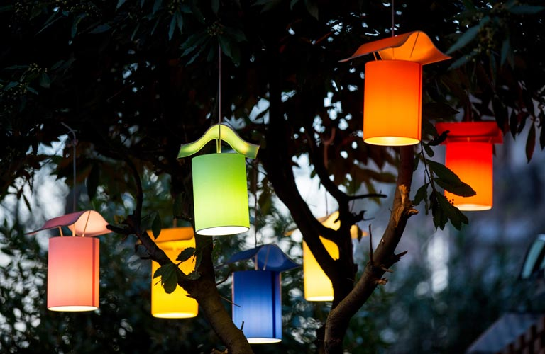 Seven colourful, lit lanterns hanging in garden tree