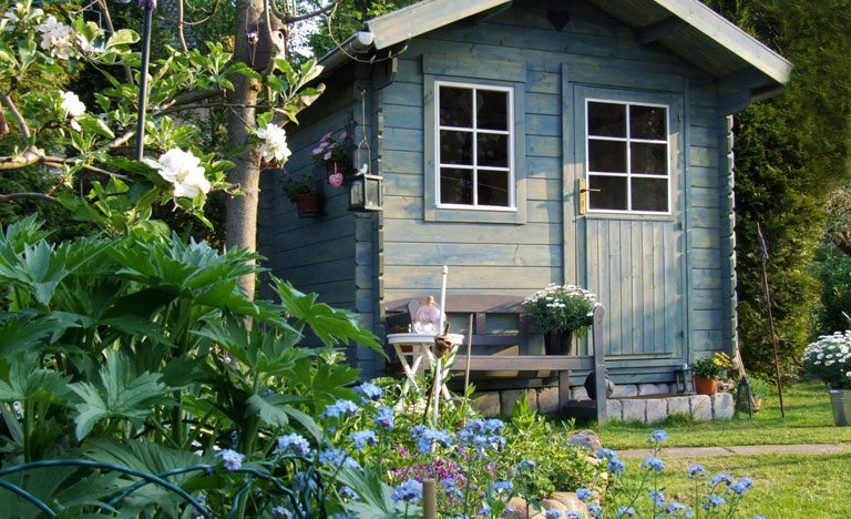 Pale blue woodpaneled summer house in a garden with plants and flowers in forefront