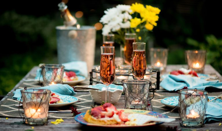 Table set for outdoor dining with dessert course of strawberry flan, creme fraiche and pink champagne by candlelight in the evening