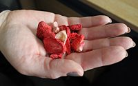 A womans hand holding a mix of dried fruits.