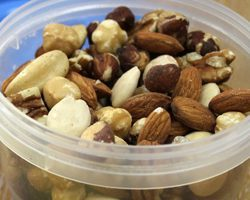 Detail of a nut mix in a plastic bowl.