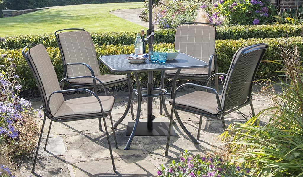 Savita 4 Seater Dining Set with Stone Check coloured cushion and parasol on a patio.