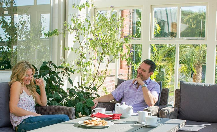 A man and woman enjoying the Palma Sofa Set in a conservatory.