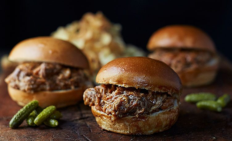 Pulled pork burgers with decorative gherkins.