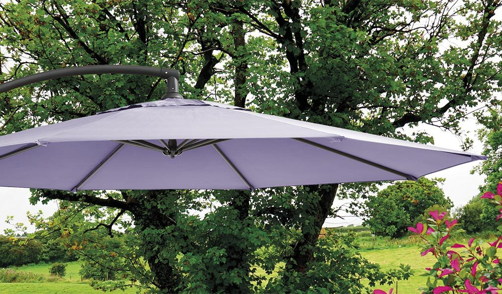 Detail of the 3m Free Arm Parasol with Wisteria coloured fabric in front of a garden.