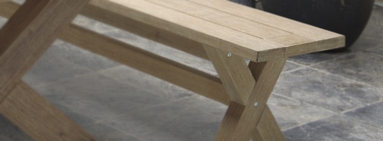 Detail of the Cora Dining Bench on a patio.