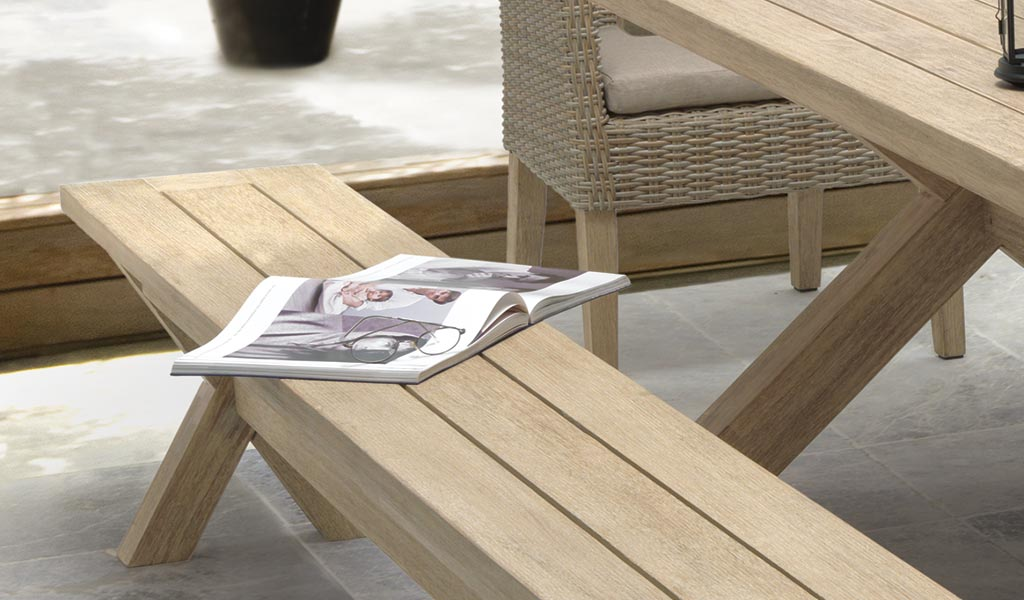 Detail of the Cora Dining Bench with a newspaper on a patio.