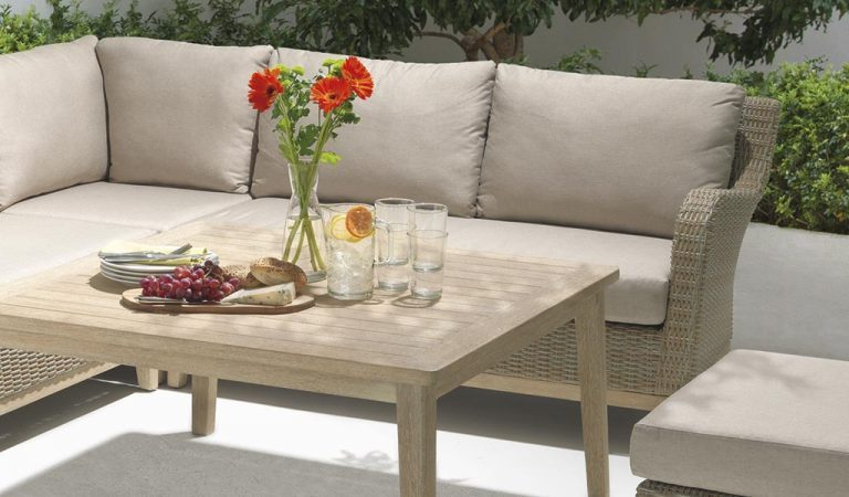 Detail of the Cora Corner Set with high table on a patio under a tree.