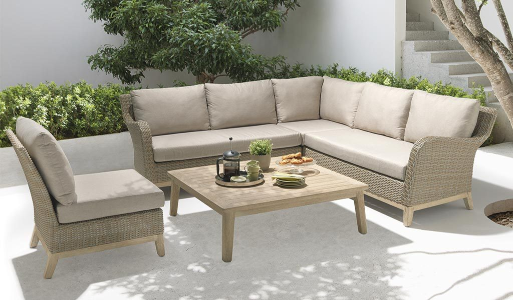 The Cora Corner Set with low table on a patio under a tree.
