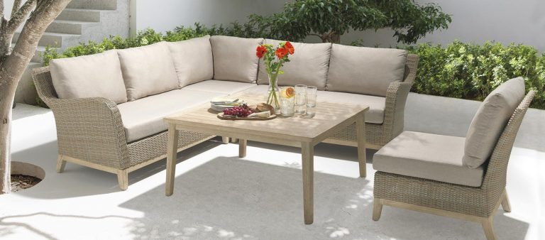 The Cora Corner Set with high table on a patio under a tree.