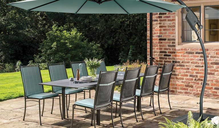 Cortona Side Chair 8 Seater Dining Set with Aqua Check cushions and 3m Free Arm Parasol on a patio.