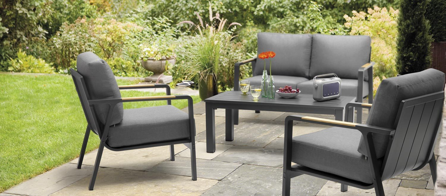 Sit four in the garden on the Paros Lounge, a high quality outdoor set with a double sofa and two armchairs. Range description / features (including bullet points): (minimum 150 words): The Paros slat top coffee table includes a minimal design and is made from durable aluminium. The weatherproof sets can stay outdoors all year round (except cushions). Hand painted, wood effect detail on the arms provide added style to turn heads, perfect for drawing guests to your garden furniture. Non-slip cushions make resting easy as you unwind outdoors. The scoop-back design gives the chairs a modern, sleek look. Sit in the shade or on a decking area of your garden and spend time with friends or family. Features: • Set includes: two scoop-back Paros Lounge Chairs, Paros Double Sofa and a Slat Coffee Table. • Material: Aluminium with hand painted, wood effect arms. • 5cm foam core seat cushions. • Weatherproof aluminium - you can leave outdoors all year round (except cushions). • Non-slip charcoal cushions. • Stain resistant cushions with shower resistance – we advise taking cushions indoors when not in use. • Seats 4. • Paros Dining sets also available.
