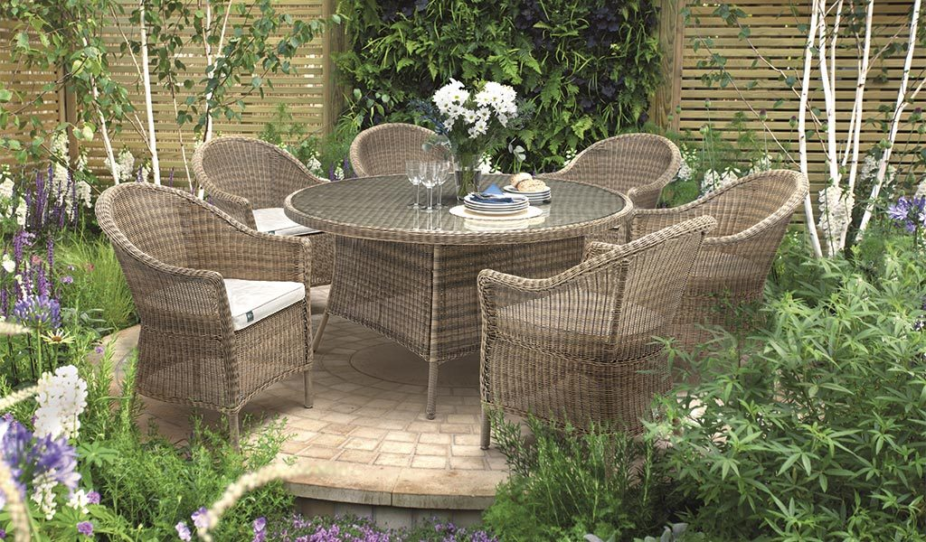 RHS Harlow Carr 6 Seat Dining Set on a round patio area surrounded by flowers.