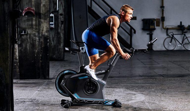 Man exercising in the basement on the Racer S Training Bike from KETTLER's fitness range.