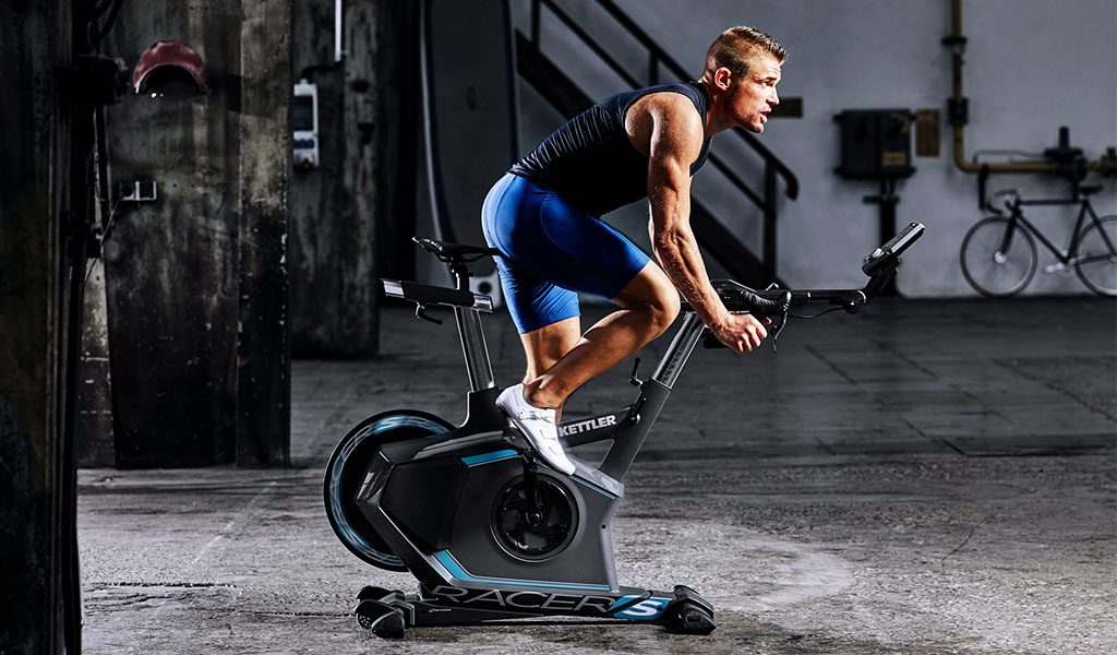 Man exercising in the basement on the Racer S Training Bike from KETTLER's fitness range.