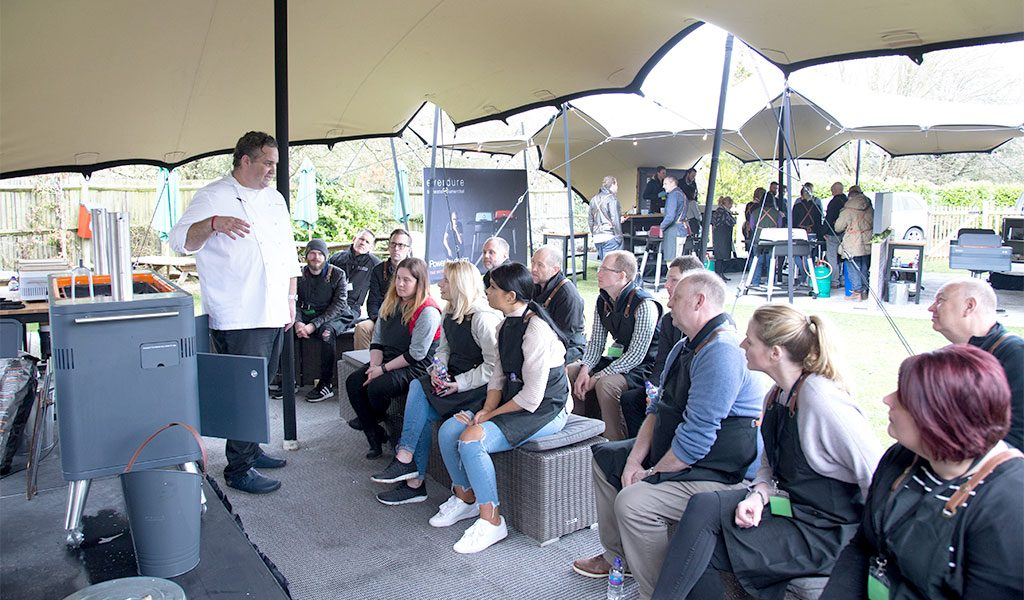 A Fat Duck chef teaching an audience how an Everdure by Heston Blumenthal HUB BBQ works.