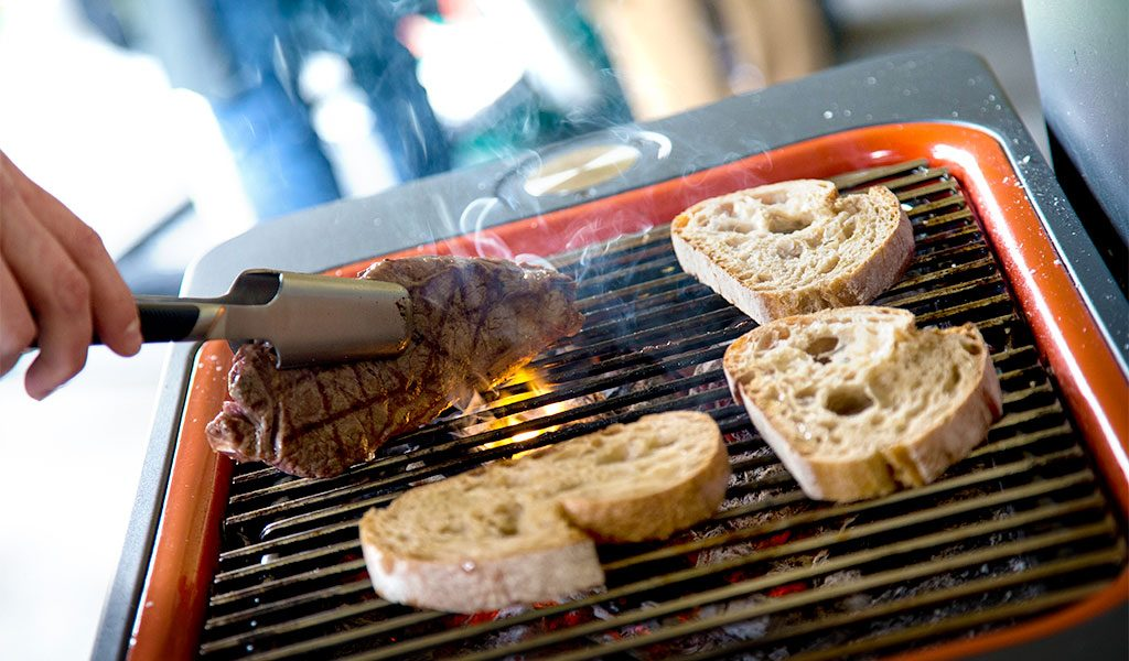 Steak and bread cooking on a Fusion charcoal BBQ at the Everdure by Heston Blumenthal BBQ experience.