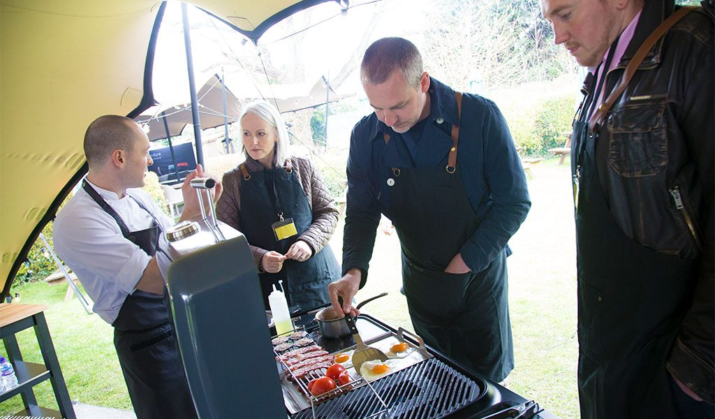 A Fat Duck chef teaching staff how to cook a full English breakfast on a Furnace gas BBQ.