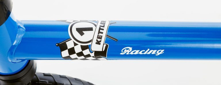 """Decal detail of Kettler's Speedy 10"""" Racing Balance Bike on a grey background."""