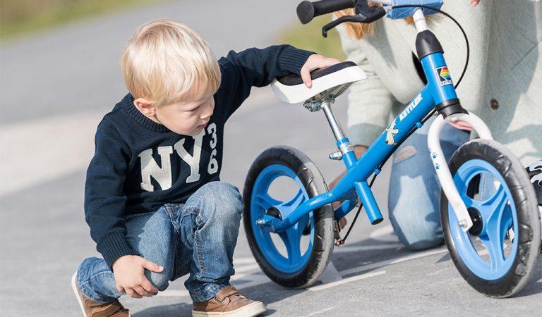 """Young boy inspecting Kettler's Speedy 12,5"""" Waldi balance bike."""