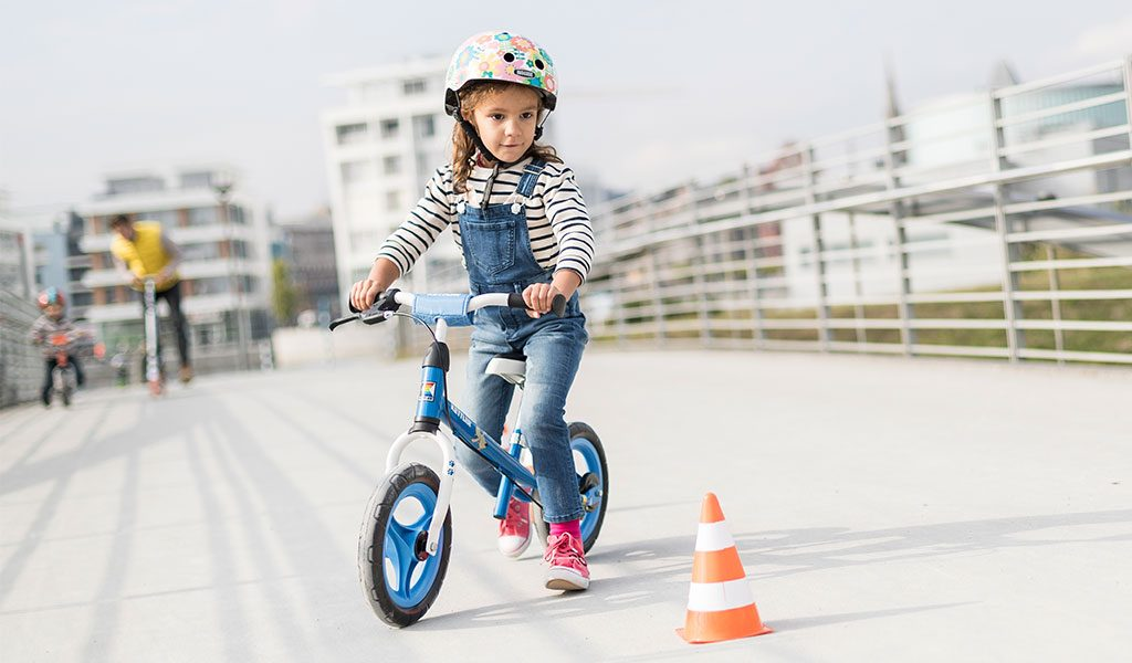 Young girl riding Kettler's Speedy 12,5: Waldi balance bike around a cone.
