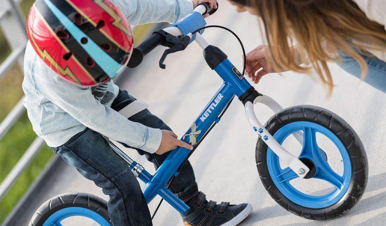 "Young boywearing a colourful helmet Kettler's Speedy 12,5"" Waldi balance bike."