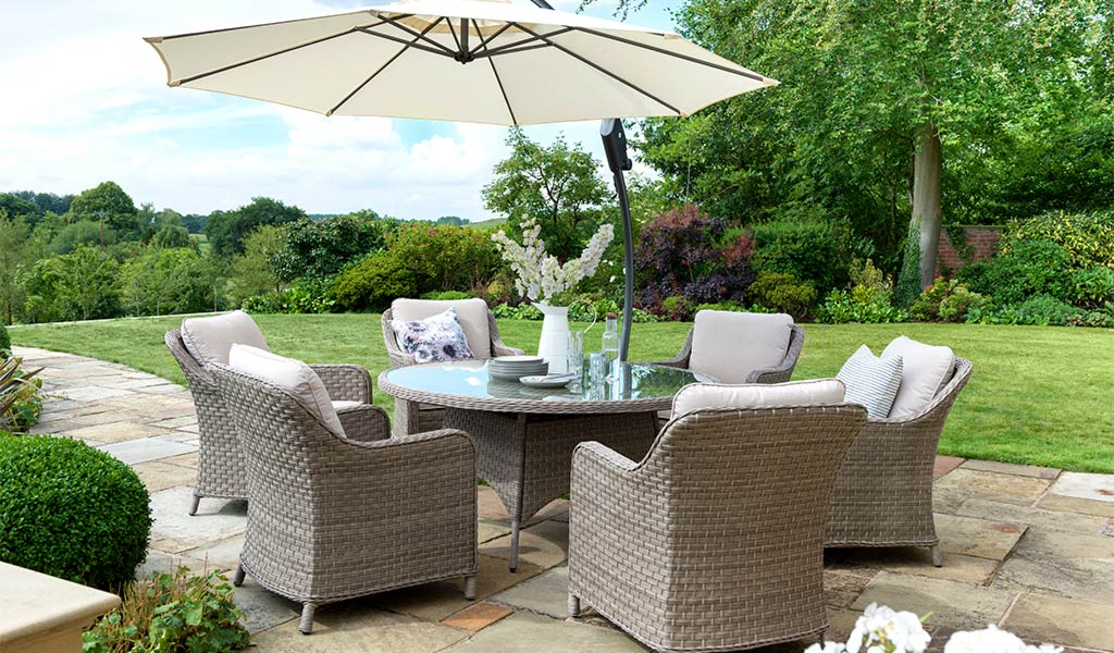 Charlbury Round Garden Dining Set with parasol on a slated patio in front of a lawn.