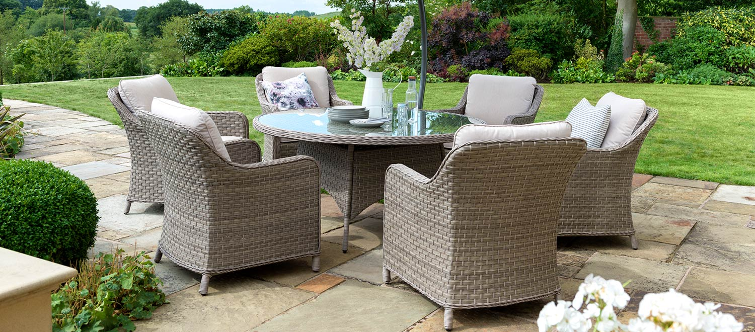Kettler's Charlbury Round Dining Set on a slated patio in front of a big lawn.