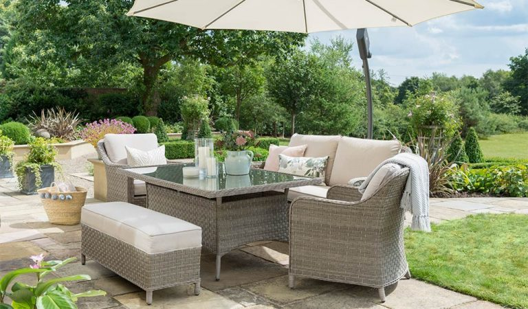 The Charlbury Dining Sofa Set with free arm parasol in a sunny garden.