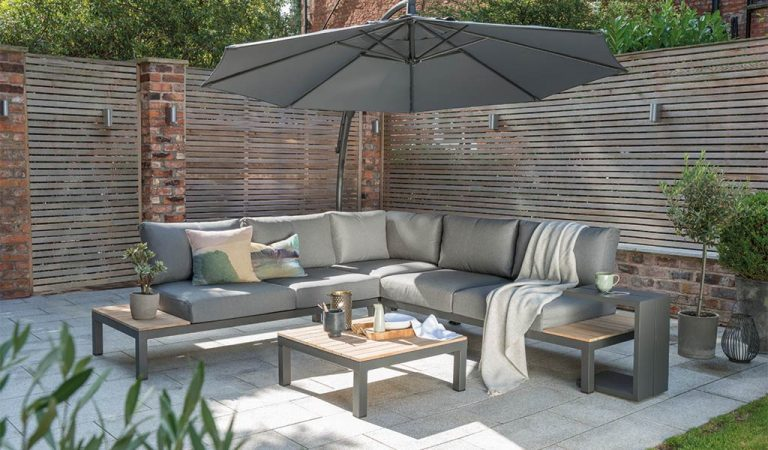 The Elba Corner Set and Elba Side Table and free arm parasol on a patio in a garden.