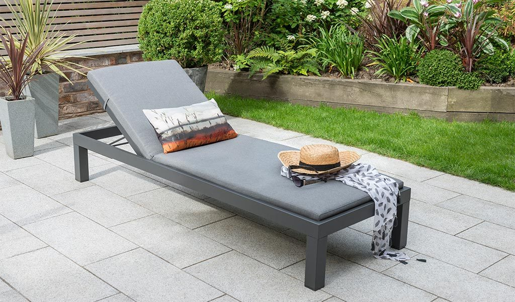 The Elba Garden Furniture Lounger on a slated patio.