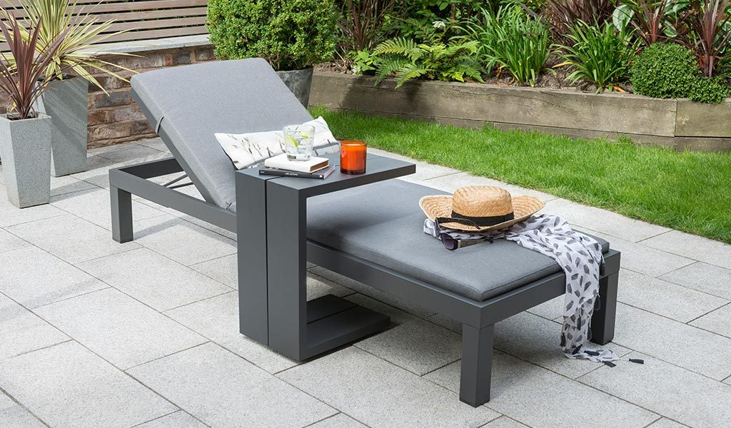 The Elba Garden Furniture Lounger with Side Table on a slated patio.