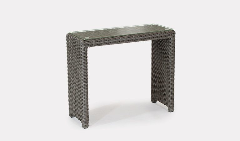 The Palma side table with glass top in rattan on a grey background.