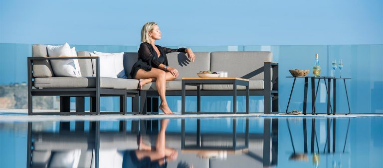 A lady sitting on the Belvedere Lounge garden furniture from the Jati & Kebon range, on a patio and in front of a swimming pool.