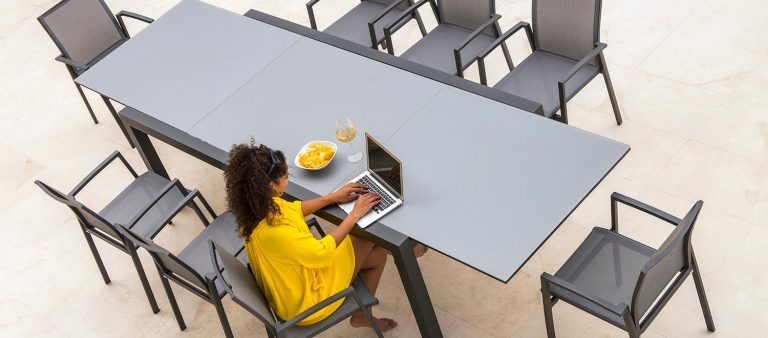 A lady sat at a Livorno Glass Extending Dining Table with 8 Elida Dining Chairs, from the Jati & Kebon range, on a patio.