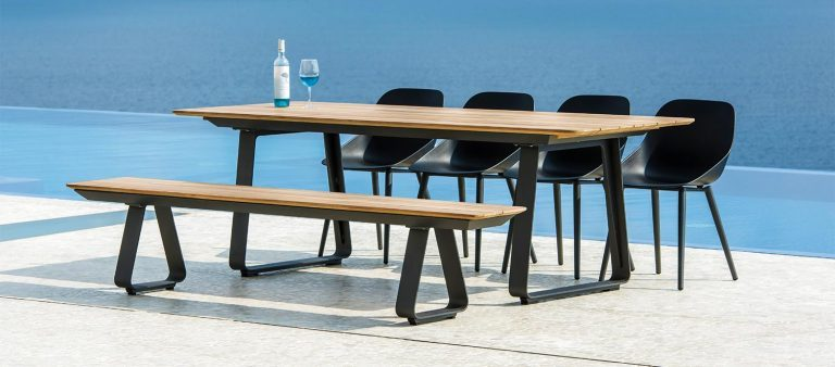 The Elko Teak Top Table with Elko Teak Top Bench and Galati Dining Chairs from the Jati & Kebon range on a patio.