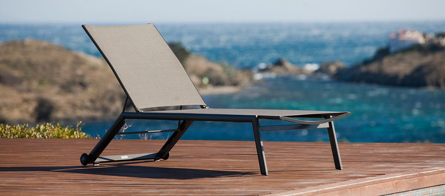 The Hydra Stacking Sun Lounger, from the Jati & Kebon range, on a wooden decking area.