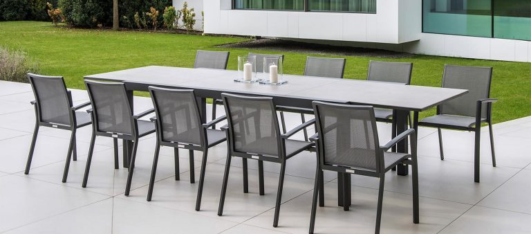 A Livorno Ceramic Extending Dining Table with 10 Elida Dining Chairs, from the Jati & Kebon range, on a patio.