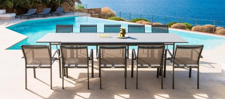 A Livorno Ceramic Extending Dining Table with 10 Elida Dining Chairs, from the Jati & Kebon range, in front of a swimming pool.