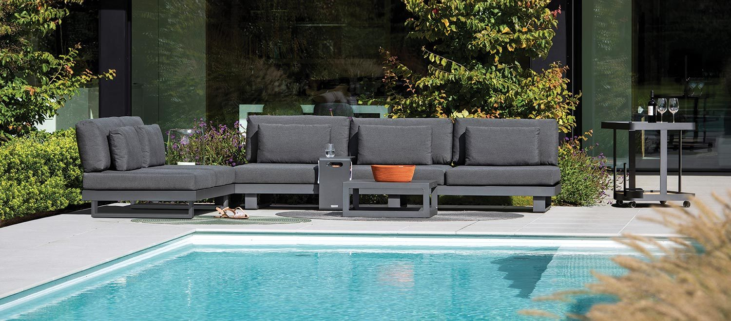The Bari-Lite Lounge garden furniture with the Bari Side Table, from the Jati & Kebon range, on a patio.