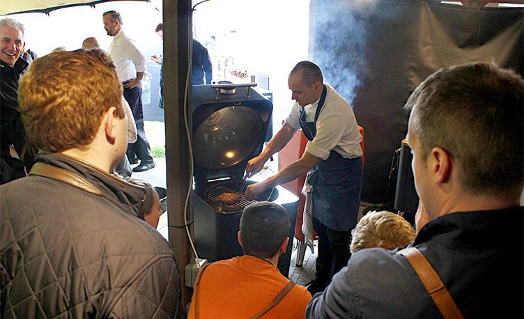 A chef from the Fat Duck Group cooking on a 4K charcoal BBQ in front of a group of people.