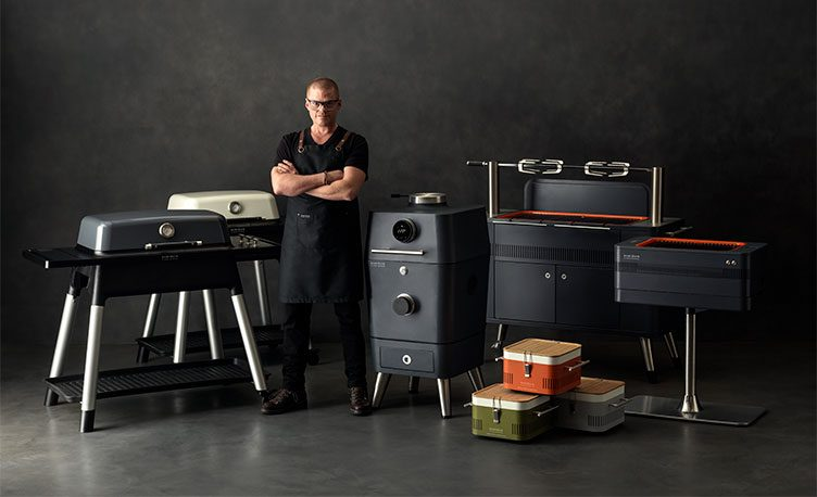 Heston Blumenthal standing in front of the full range of Everdure by Heston Blumenthal BBQ's.
